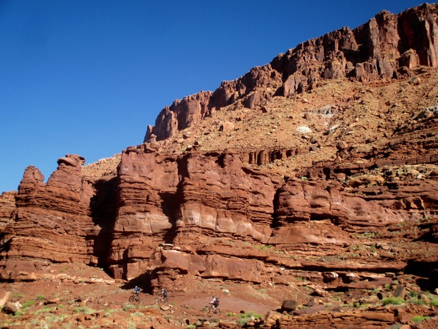 Massive red rock formations dwarf the riders